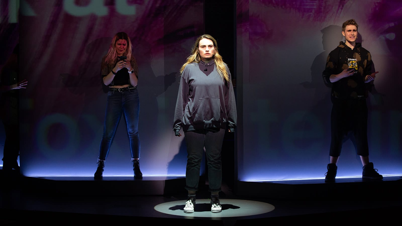 Kathryn Gallagher as Bella (center) and members of The Chorus, Jane Bruce and John Cardoza in American Repertory Theater's Jagged Little Pill
